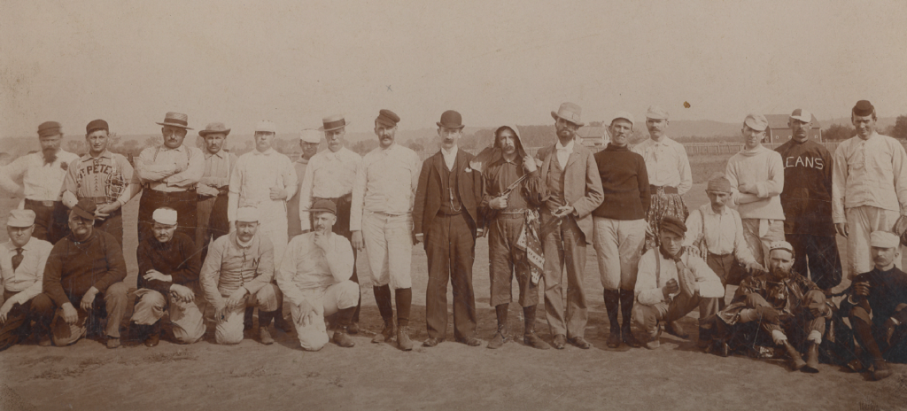 This photograph shows baseball players from the Fats versus the Leans game in St. Peter in 1894. This game was played as a charitable event in order to raise money for the victims of the Hinckley fire. Future Gov. John A. Johnson is shown as the man in white standing at the far right.
